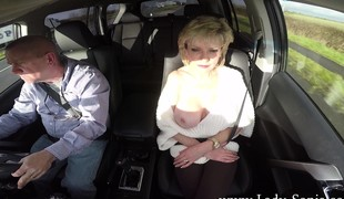 Lustful blonde cougar relative to fat breasts pleases her snatch in the car