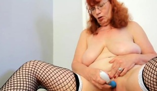 Saggy mature titties on the top of this masturbating redhead